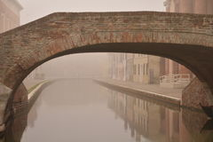 Comacchio, canal bridge in winter. Ferrara, Emilia Romagna, Italy. A bridge over a canal in the colorful Italian village of Comacchio. Old brick bridge across Stock Photos
