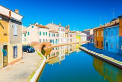Comacchio, Italy: View of the canal with bridge and colored houses reflected in the water. Comacchio - October 2016, Emilia Romagna, Italy: View of the canal Stock Image