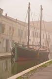Comacchio, kanaalbrug en oud schip in de winter Ferrara, Emilia Romagna, Italië Stock Foto