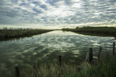 Comacchio valley lagoon. Lagoon channel with a cloudy sky stock image
