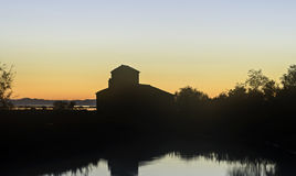 Comacchio valley lagoon. Fisherman house Silhouette in a Sunset on the Po river lagoon royalty free stock images
