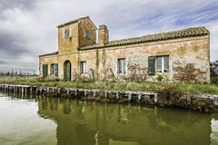 Comacchio valley lagoon. Old red stone fisherman house in the lagoon stock image