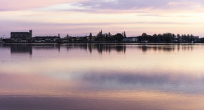 Comacchio valley lagoon. Sunrise on the Po river lagoon with Comacchio church silhouette in the background royalty free stock photography