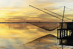 Comacchio valley lagoon. Sunrise on the Po river lagoon with a view of fishermen houses and nets stock photos