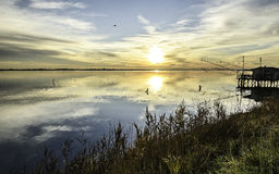 Comacchio valley lagoon. Sunrise with a view of old wood fisherman houses stock photography