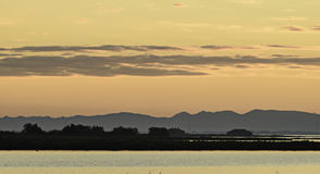 Comacchio valley lagoon. Sunset on the Po river lagoon with silhouette in the background stock photography