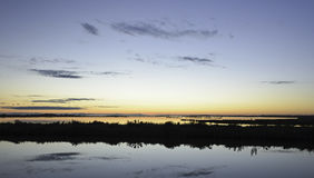 Comacchio valley lagoon. Sunset in the lagoon with a silhouette in the foreground royalty free stock photo