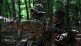 Comandante del pelotón de los guerreros de la guerrilla que da instrucciones sus combatientes en los arbustos del bosque metrajes