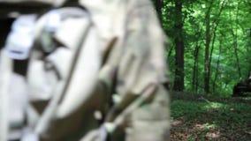 Comandante del pelotón de los guerreros de la guerrilla que da instrucciones sus combatientes en los arbustos del bosque almacen de video