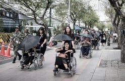 Comandi all'anziano di aiuto sulla sedia a rotelle alle devozioni per il funerale di Ki immagini stock