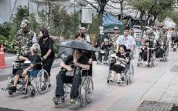 Comandi all'anziano di aiuto sulla sedia a rotelle alle devozioni per il funerale di Ki immagine stock