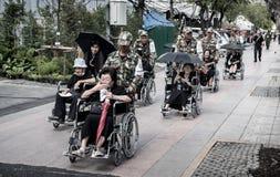 Comandi all'anziano di aiuto sulla sedia a rotelle alle devozioni per il funerale di Ki fotografie stock