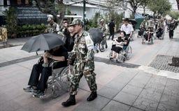 Comandi all'anziano di aiuto sulla sedia a rotelle alle devozioni per il funerale di Ki fotografia stock