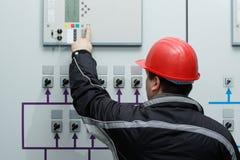 Comando di elasticità del tecnico nel centro di controllo della centrale elettrica Fotografie Stock Libere da Diritti