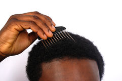 Comb the Afro. This is an image of a black man combing his afro royalty free stock photo