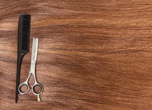 Comb and barber scissors on  background of beautiful brown hair. Royalty Free Stock Photo