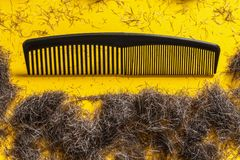 Comb and beard clippings on yellow background Royalty Free Stock Photos