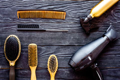 Comb brushes, hairdryer and hairspray on grey wooden background top view Stock Photo