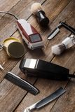 Electric hair trimmers and brushes. Comb, electric hair trimmers, wax, straight razors and brushes on the wooden surface, close-up. Barbershop tools stock photos