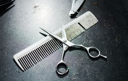 Comb and scissors on a dirty table. Comb and scissors on a dirty hairdresser table Royalty Free Stock Image