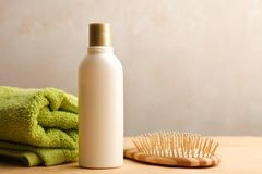 Comb, shampoo and towel. On a wooden table on a neutral background stock images