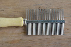 Comb with teeth away and fine side for pet on wooden board Stock Photo