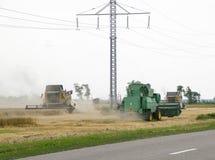 Combain si raccoglie sul raccolto del grano Macchinario agricolo nel campo Immagini Stock Libere da Diritti