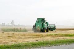 Combain si raccoglie sul raccolto del grano Macchinario agricolo nel campo Immagine Stock Libera da Diritti