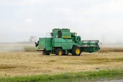 Combain si raccoglie sul raccolto del grano Macchinario agricolo nel campo Fotografia Stock Libera da Diritti