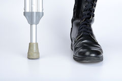 Combat boot and crutch Royalty Free Stock Images