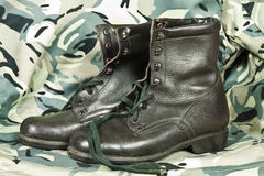 Combat boots. Old model high combat boots on camouflage background Stock Images