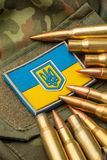 Combat bullets on the background of the Ukrainian flag. Camouflage symbol of the Ukrainian army stock photography