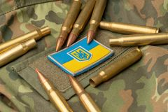Combat bullets on the background of the Ukrainian flag. Camouflage symbol of the Ukrainian army royalty free stock photos