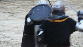 Combat d'épée entre deux hommes portant les costumes historiques d'armure et les casques en acier banque de vidéos