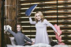 Combat d'oreiller de maison du ` s de soeur sur le lit heureux photo stock