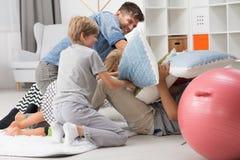 Combat d'oreiller entre le père et les enfants images stock