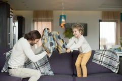 Combat d'oreiller entre le père et le petit fils dans le salon Images libres de droits
