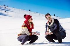 Combat de boule de neige Couples de l'hiver ayant l'amusement jouer dans la neige à l'extérieur Jeunes couples multi-raciaux heur Photographie stock libre de droits