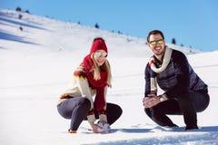 Combat de boule de neige Couples de l'hiver ayant l'amusement jouer dans la neige à l'extérieur Jeunes couples multi-raciaux heur Photos stock