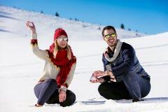 Combat de boule de neige Couples de l'hiver ayant l'amusement jouer dans la neige à l'extérieur Jeunes couples multi-raciaux heur Images stock