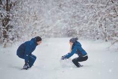 Combat de boule de neige Couples de l'hiver ayant l'amusement jouer dans la neige à l'extérieur Photographie stock libre de droits