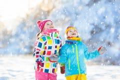 Combat de boule de neige d'hiver d'enfants Jeu d'enfants dans la neige Photos stock