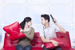 Combat de couples sur le sofa rouge - d'intérieur Images stock