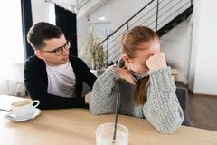 Combat de couples Un jeune homme essaye d'avoir une conversation, alors qu'il a été ignoré par son amie images stock