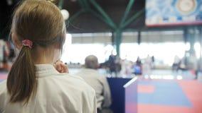 Combat de observation de fille de sports de karaté d'adolescent sur le tatami - spectateur - concurrence de karaté - ralenti clips vidéos