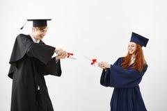 Combat de sourire de diplômés gais avec des diplômes au-dessus du fond blanc Photographie stock libre de droits