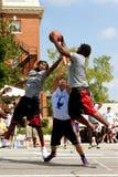 Combat de trois hommes pour le rebond dans le tournoi extérieur de basket-ball de rue Image stock