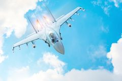 Combat fighter jet on a military mission with weapons - rockets, bombs, weapons on wings, with fire afterburner engine nozzles, fl royalty free stock image