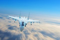 Combat fighter jet on a military mission with weapons - rockets, bombs, weapons on wings flies motion blur high in the sky above t stock photo