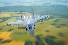 Combat fighter jet on a military mission with weapons - rockets, bombs, weapons on wings, at high speed with fire afterburner engi. Ne nozzles, flies over the stock images